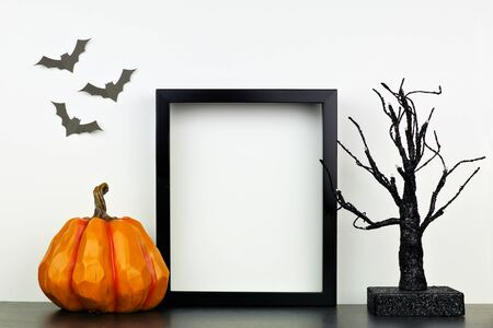 Mock up black frame with Halloween pumpkin and spooky tree decor on a shelf against a white wall