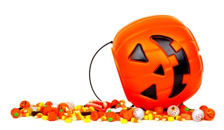 Halloween Jack o Lantern bucket with spilling candy, side view isolated on a white background