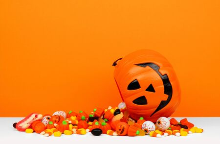 Halloween Jack o Lantern bucket with spilling candy, side view on an orange background