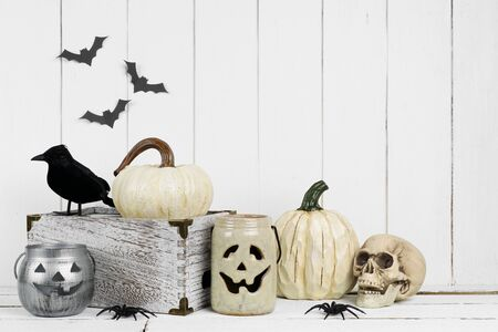 Black and white Halloween decor display against a rustic white wood background with copy space