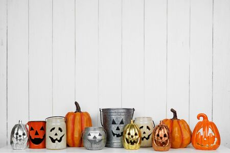 Halloween decor display of Jack o Lantern candle holders against a white wood background