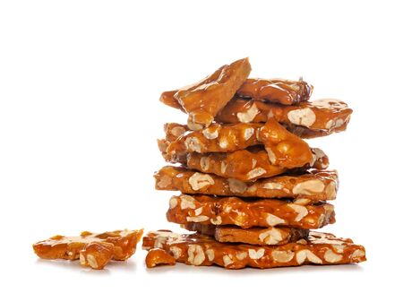 Stack of traditional peanut brittle candy pieces, isolated on a white background