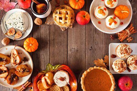 Marco de escena de mesa de otoño de tartas, aperitivos y postres, vista superior sobre un fondo de madera con espacio de copia Foto de archivo