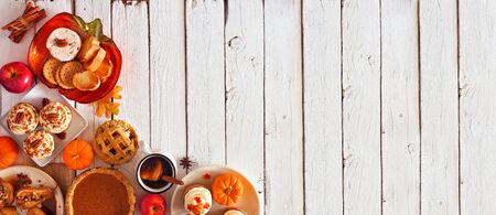 Autumn table scene corner border banner of pies, appetizers and desserts, top view over a white wood background with copy space