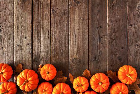 Borde inferior otoñal de calabazas y hojas de otoño, vista superior sobre un fondo de madera rústica