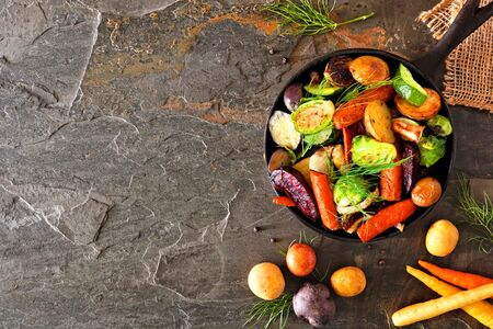 Cast iron skillet of roasted autumn vegetables, above view side border over a dark stone background