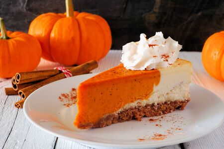 Slice of pumpkin cheesecake with whipped cream, side view table scene