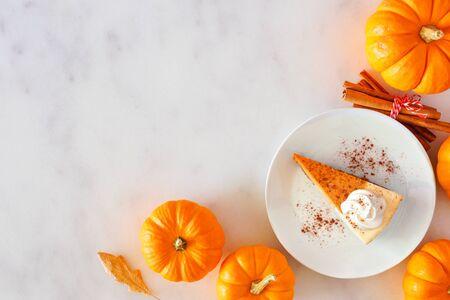 Plakje pompoentaart cheesecake met slagroom, bovenaanzicht hoekrand op een marmeren achtergrond