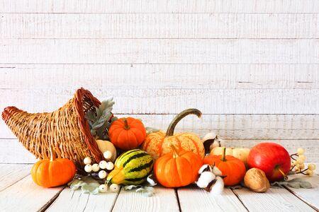 Corne d'abondance de Thanksgiving remplie de légumes d'automne et de citrouilles sur fond de bois blanc rustique