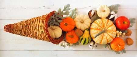 Thanksgiving cornucopia filled with autumn pumpkins and vegetables, top view against white wood
