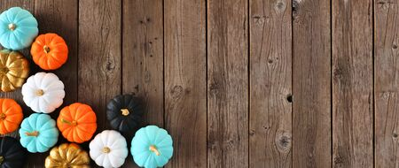 Autumn corner border banner of colorful pumpkins on a rustic wood background. Top view with copy space.