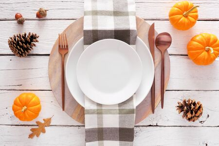 Fall harvest or thanksgiving dinner table setting, above view on white wood