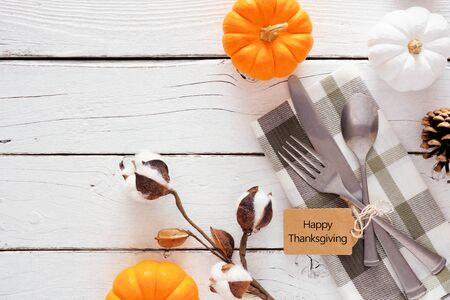 Happy Thanksgiving gift tag with silverware, check print napkin, pumpkins and decor over a white wood background Zdjęcie Seryjne