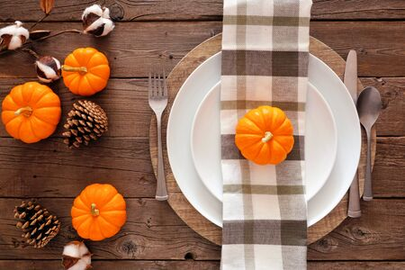 Autumn harvest or thanksgiving dinner table setting, top view on a rustic wood background
