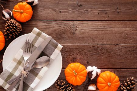 Fall corner border with dinner plate, silverware, check print napkin, pumpkins and pine cones against a rustic wood background Zdjęcie Seryjne