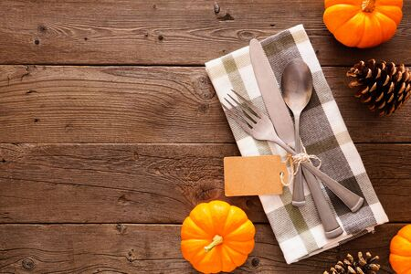Blank gift tag with silverware, check print napkin, and autumn decor, top view side border against a rustic wood background