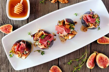 Fig appetizers with blue cheese, prosciutto and honey, above view on a plate over wood 版權商用圖片