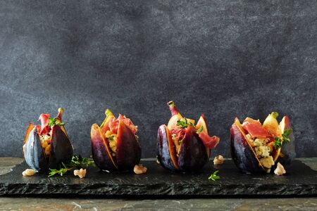 Fig appetizers with blue cheese, prosciutto and honey in a row on a state serving board