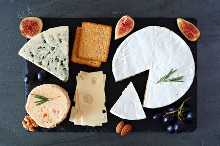 Cheese board with a selection of cheeses, crackers, figs and nuts, above view on a slate serving board
