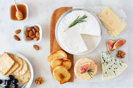 Cheese platter with a selection a cheeses, crackers, figs, nuts and honey, overhead table scene on a marble background 写真素材
