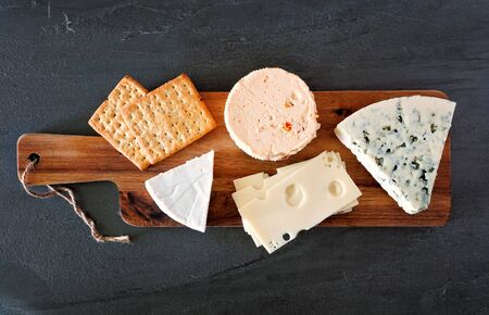 Cheese platter with a selection of cheeses on wooden serving board on a slate background