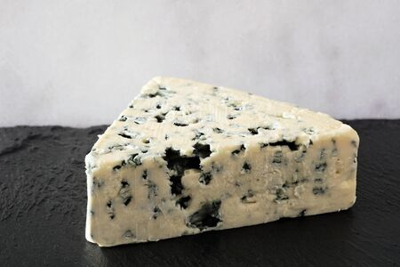 Wedge of blue cheese on a black and white background 免版税图像