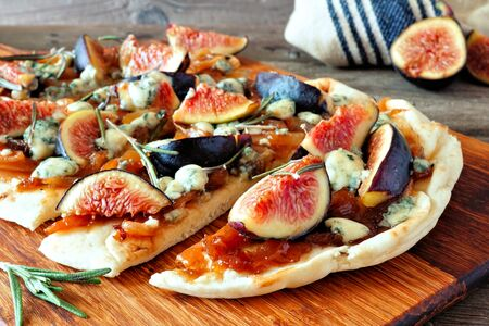 Autumn flat bread with figs, caramelized onions, blue cheese and rosemary, close up on a wood board Reklamní fotografie