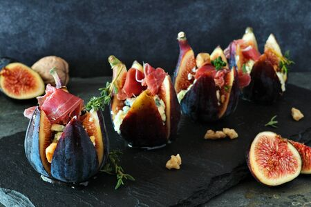 Fig appetizers with blue cheese, prosciutto and honey close up on dark background