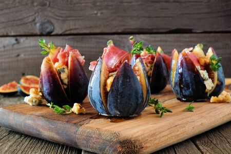 Fig appetizers with blue cheese, prosciutto and honey on a wood serving board 版權商用圖片