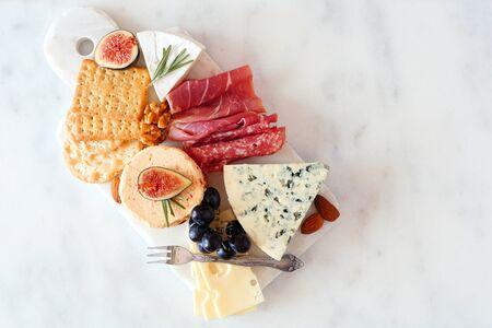 Plato de aperitivo con una variedad de quesos y carnes, vista superior en mármol blanco