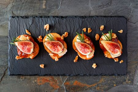 Appetizers with figs, brie cheese and walnuts, above view on a slate platter