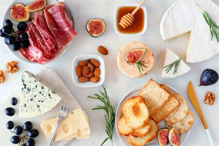 Assorted cheeses and meat appetizers, above view table scene on a marble background