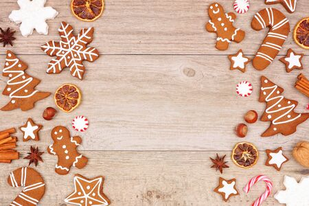 Christmas gingerbread cookies, candy and baking items, double side border on a wood background Imagens