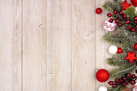 Kerst zijrand met rode en witte ornamenten en takken, boven uitzicht op een grijze houten achtergrond