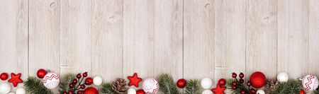 Christmas long border banner with red and white ornaments and branches, top view on a gray wood background Imagens