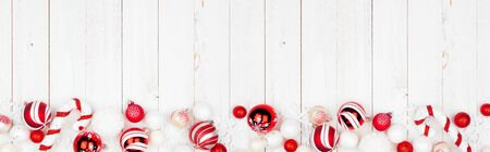 Christmas bottom border banner with red and white ornaments, top view on a white wood background