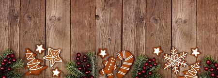 Christmas gingerbread cookies and tree branches, top view border banner on a wood background