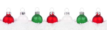 Christmas border of red, green and white baubles resting in snow isolated on a white background