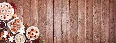Christmas baking corner border banner with assorted sweets and cookies, overhead on a rustic wood background Stock Photo