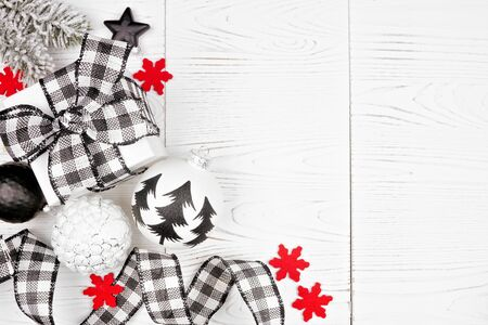 Christmas corner border of black and white checked buffalo plaid ribbon, gifts and ornaments, overhead on a white wood background Stock Photo