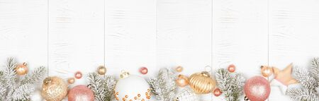 Christmas long border banner of snowy branches and dusty rose, gold, and white ornaments on a white wood background Imagens