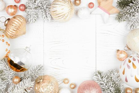 Christmas frame of snowy branches and dusty rose, gold, and white ornaments on a white wood background Stock Photo