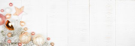 Christmas corner border banner of snowy branches and dusty rose, gold, and white ornaments on a white wood background