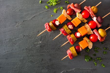 Skewer appetizers with meat, cheeses and pickles, above view over a dark slate background with copy space