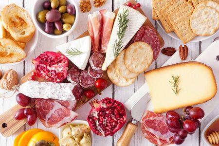 Charcuterie board of assorted cheeses, meats and appetizers, top view table scene over white wood Foto de archivo