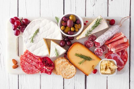 Serving platter of assorted meats, cheeses and appetizers, top view on white wood