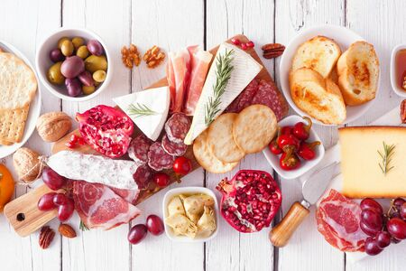 Charcuterie board of assorted cheeses, meats and appetizers, above view table scene over white wood