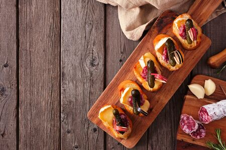 Crostini appetizer board with baked brie, sausage and pickles, top view serving scene over rustic wood with copy space