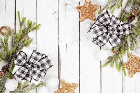 Christmas double corner border with branches, ornaments and black and white checked buffalo plaid gifts, above view on a white wood background Stock Photo