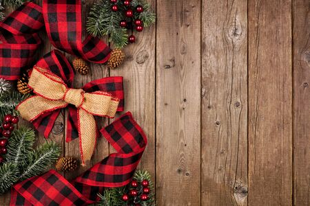 Christmas side border with red and black checked buffalo plaid ribbon, burlap and branches, overhead view on a wood background